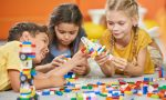 Group of kids playing with plastic blocks.